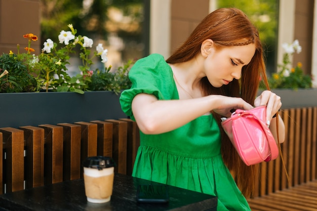Close-up of worried anxious young woman sitting at table in outdoor cafe terrace nervously looking in bag for keys or wallet, searching lost things, blurred background, selective focus.