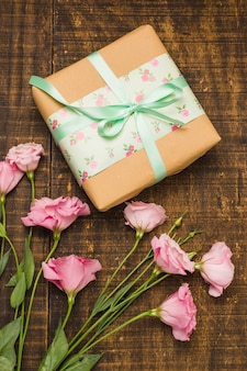 Close-up of wrapped parcel and pink fresh flower on table