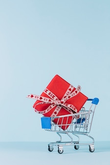 Close-up of wrapped red gift box in shopping cart on blue backdrop