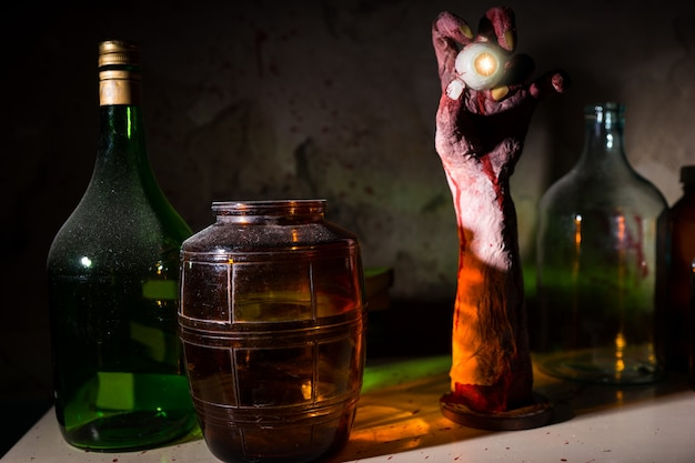 Close up of wrinkled hand with eyeball between glass jars with blood spattered wall in a halloween horror concept