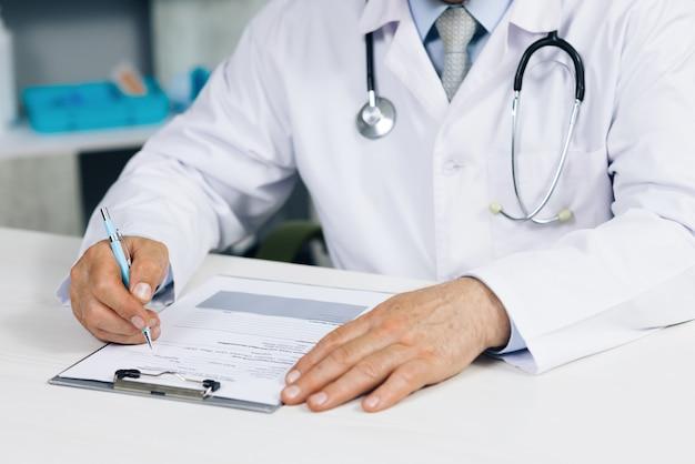 Close up wrinkled male doctor writing information in medical registration journal