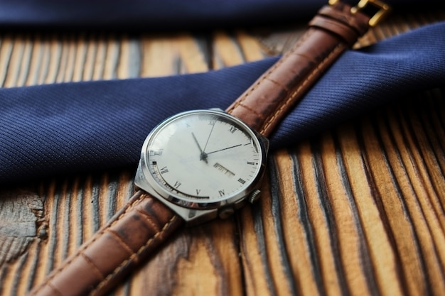 Close up of wristwatch with leather strap on wooden background
