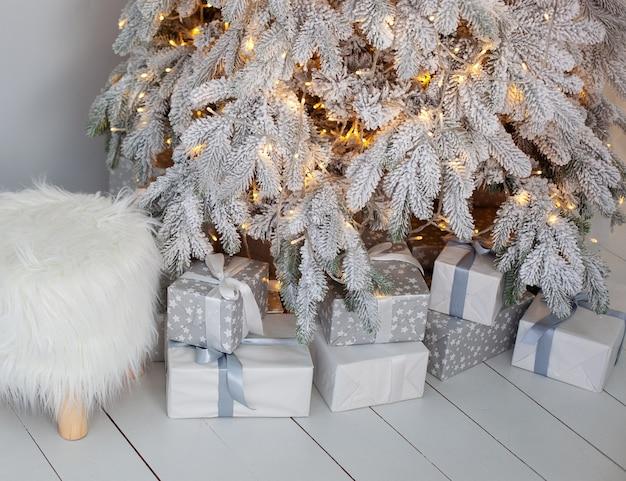 リビングルームのクリスマス雪の木の近くの床にクローズアップのクリスマスプレゼント。