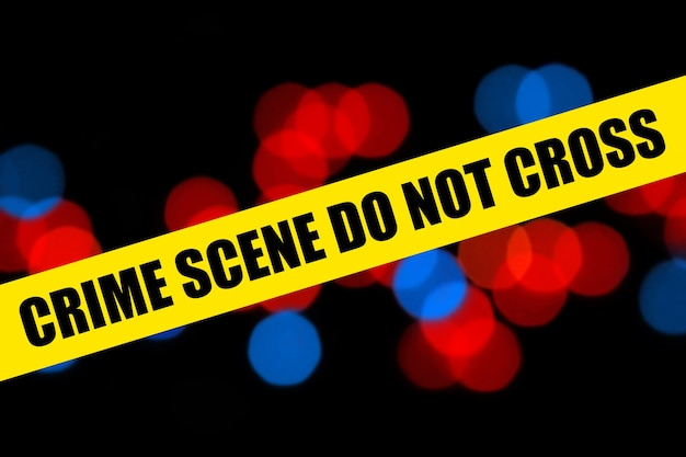 Close up yellow barricade tape with crime scene do not cross words over police background of blurred red and blue police lights bokeh