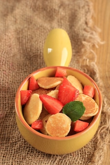 Close up yellow bowl full of tiny pancake or popular as cereal pancake, popular viral snack during quarantine in 2020. served above jute brown background, vertical version picture