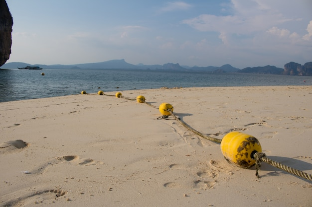Close-up yellow buoys with rope  on the beach