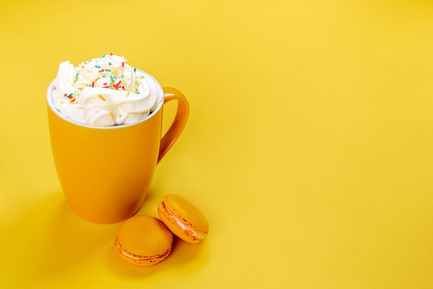 Close up of yellow coffee cup and french macaroons on yellow background.