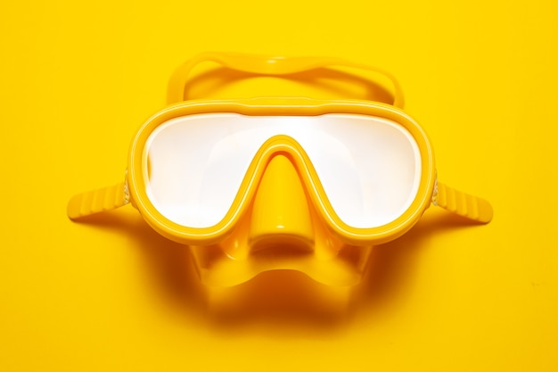 Close-up of yellow diving goggles, isolated on yellow studio background.