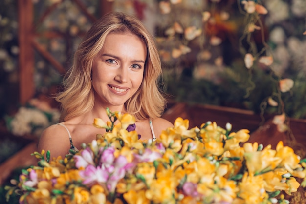 Close-up of yellow flowers bouquet in front of blonde young woman looking to camera