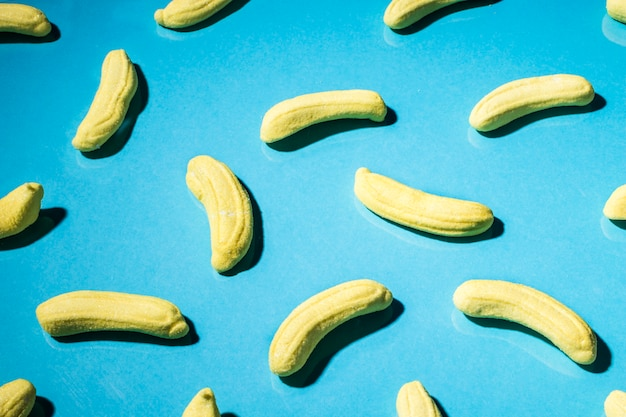 Close-up of yellow gummy banana candies on blue backdrop