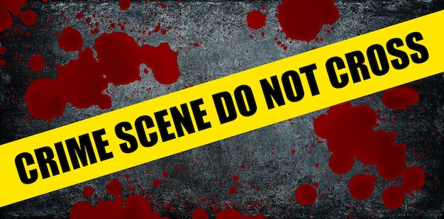 Close up yellow police barricade tape with crime scene do not cross words over blood stains splattered on dark grey stone background