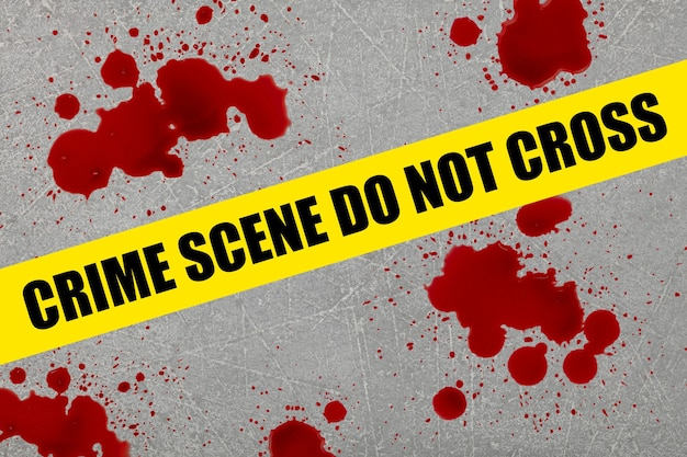 Close up yellow police barricade tape with crime scene do not cross words over blood stains splattered on grey stone floor background