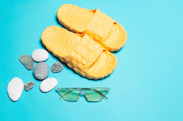 Close-up of yellow slippers and sunglasses near pebbles  background.