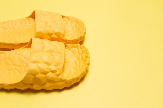 Close-up of yellow slippers on yellow background with copy space.