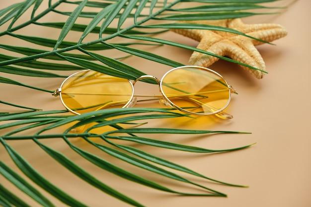 黄色のサングラスとヤシの葉をベージュの表面にクローズアップ