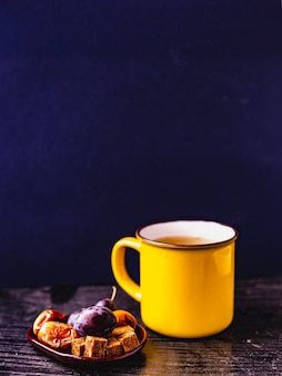 Close up yellow tea cup  on wooden  stand, dark blue background,  fruits on a little ceramic plate