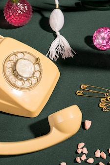 Close up yellow telephone next to girly items