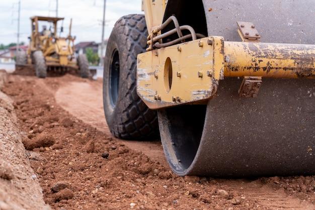 Крупным планом желтый вибрационный грунт и автогрейдер гражданского уплотнителя, работающих на строительной площадке