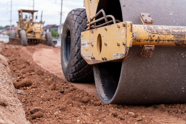 Close up yellow vibratory soil and motor grader civil compactor working on road construction site