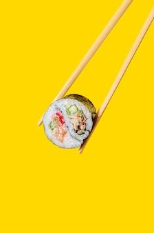 Закройте вверх по роллу инь-ян с лососевой рыбой, угрем и огурцом на палочках для еды на желтом фоне.