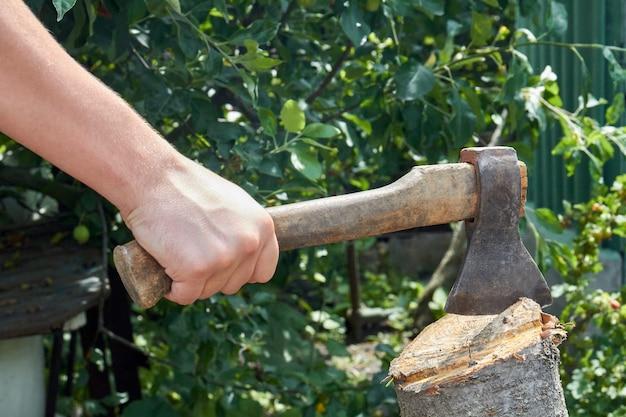 Крупным планом рука йог с топором, резающий бревно. инструмент с деревянной ручкой.
