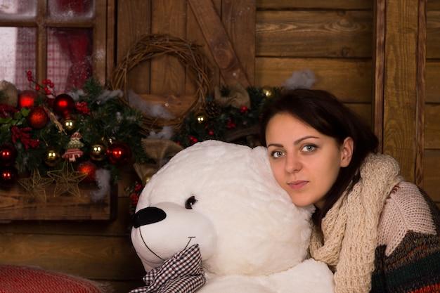 クリスマスの装飾と木製の壁の背景に白いクマの人形を抱き締める冬の衣装で若い大人の女性を閉じます。