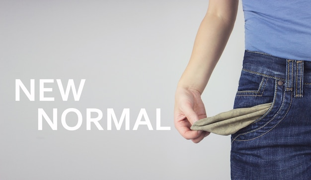 Close up young adult woman in jeans showing empty pocket with inscription new normal.