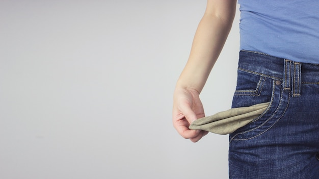 Close up young adult woman in jeans showing empty pocket.
