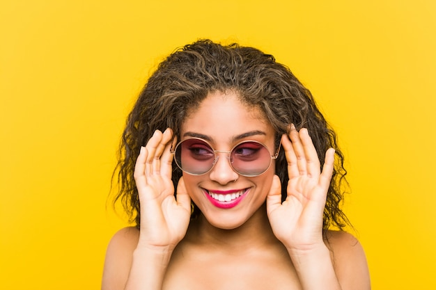 Close up of a young african american beautiful and make-up woman wearing sunglasses