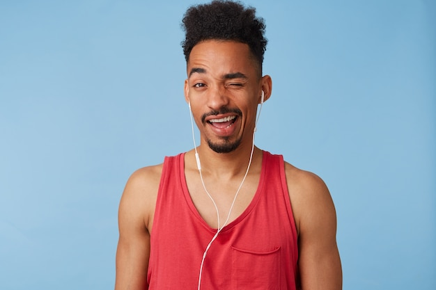 Close up of young african american guy in a great mood,wears in a red jersey, listens cool music, winks and smiles broadly stands.