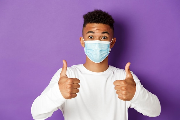 Close-up of young african-american guy showing thumbs up on purple