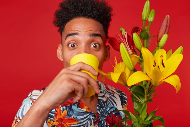 Close up of young african american man in hawaiian shirt, surprised looks at the camera and drinking water from a yellow glass, holds yellow and red flowers bouquet, stands over red background.