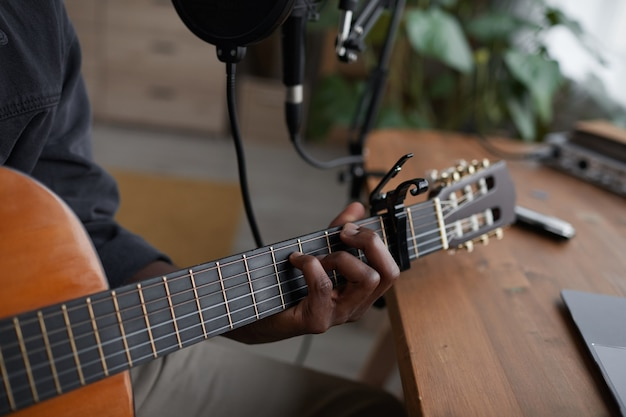 Close up of young african-american man playing guitar in home recording studio, copy space