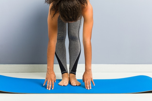 Close up of a young african american sporty woman practicing yoga using a mat