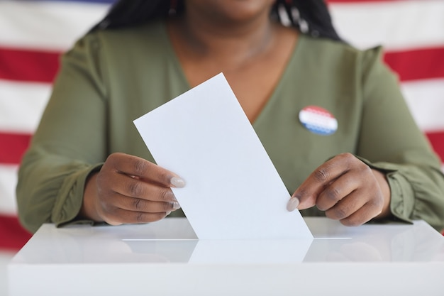 Close up of young african-american woman putting vote bulletin in ballot box while standing against american flag on election day, copy space