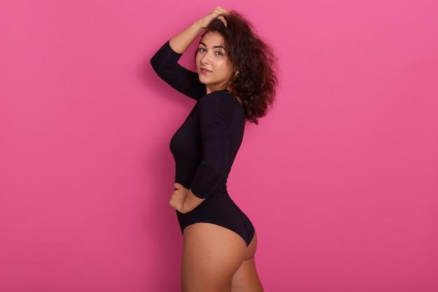 Крупным планом молодая и страстная женщина в черном комбидрессе с длинным рукавом, держит руки на голове и бедрах, имеет темные волнистые волосы, копирует пространство для рекламы.