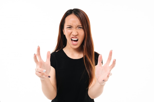 Close-up of young annoyed angry asian woman holding hands in furious gesture, looking at camera