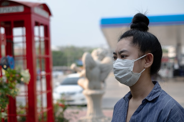 Close up of young asia woman standing putting on a respirator n95 mask to protect from airborne respiratory diseases