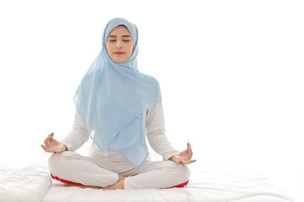 Крупным планом молодая азиатская арабская женщина, сидящая на кровати