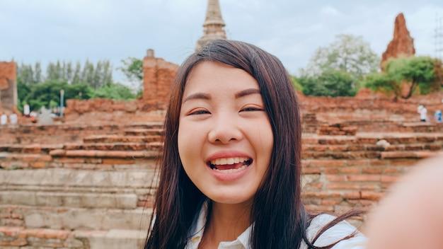 La giovane donna asiatica del blogger del viaggiatore con zaino e sacco a pelo del primo piano esamina la parte anteriore sullo smartphone