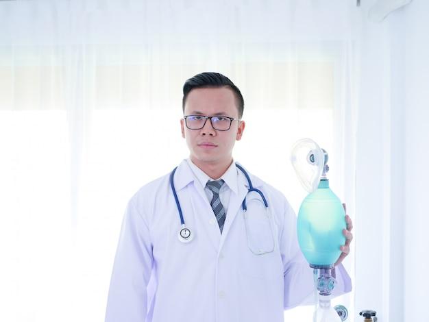 Закройте молодой азиатский врач холдинг кислородной маски в комнате неотложной помощи.