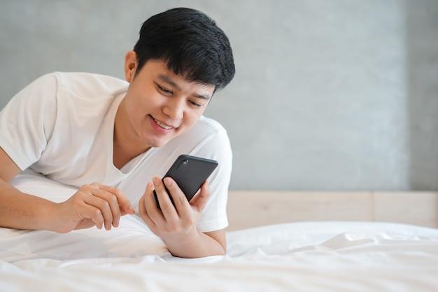 週末にベッドの上で携帯電話を演奏若いアジア人男性を閉じる