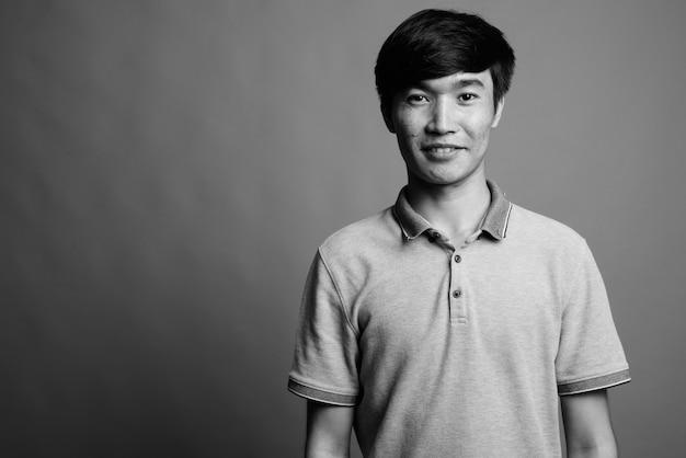 Close up of young asian man wearing gray polo shirt