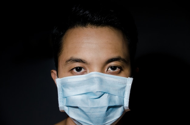 Close up of young asian man wearing hygienic mask with dark blackground