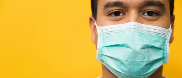 Close up young asian man wearing protection face mask against coronavirus on yellow