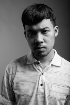 Close up of young asian man wearing striped polo shirt