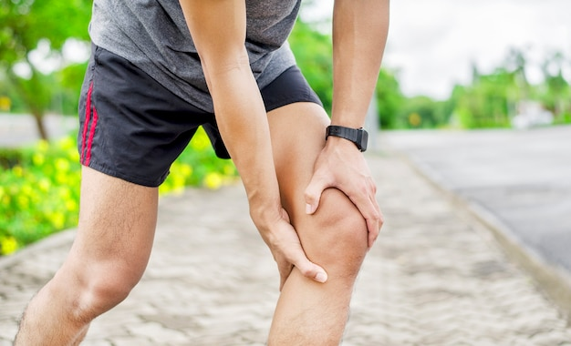 Close up of young asian sports man has pain at muscles and joints during outdoor exercise, over trainning or running and sport injuty concept