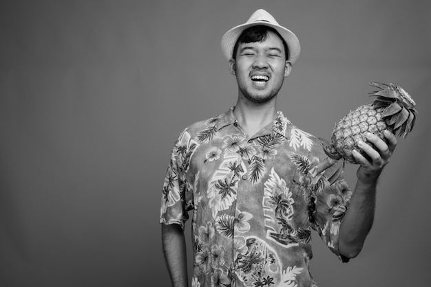 Close up of young asian tourist man holding pineapple ready for vacation