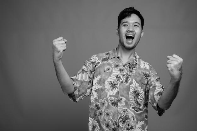 Close up of young asian tourist man wearing hawaiian shirt ready for vacation