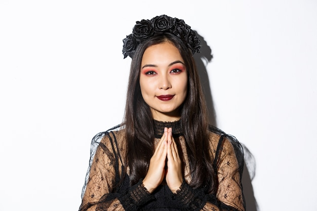 Close-up of young asian woman in black gothic dress and wreath holding hands in pray, girl wearing witch costume and celebrating halloween.